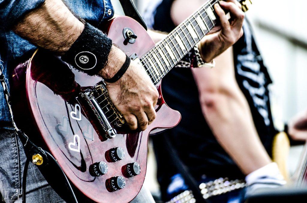 Chłopak gra na gitarze w zespole
