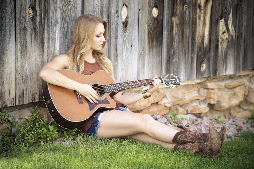Dziewczyna z gitarą występuje pod stodołą