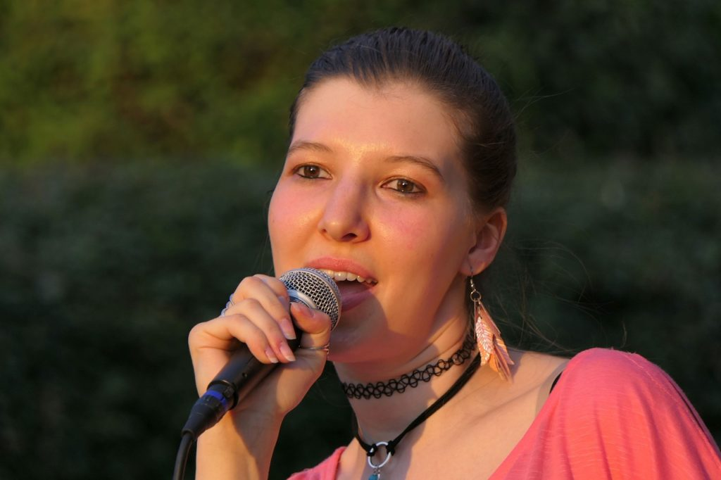 Dziewczyna wykonuje plenerowy utwór