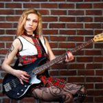Dziewczyna gra piosenki na gitarze basowej