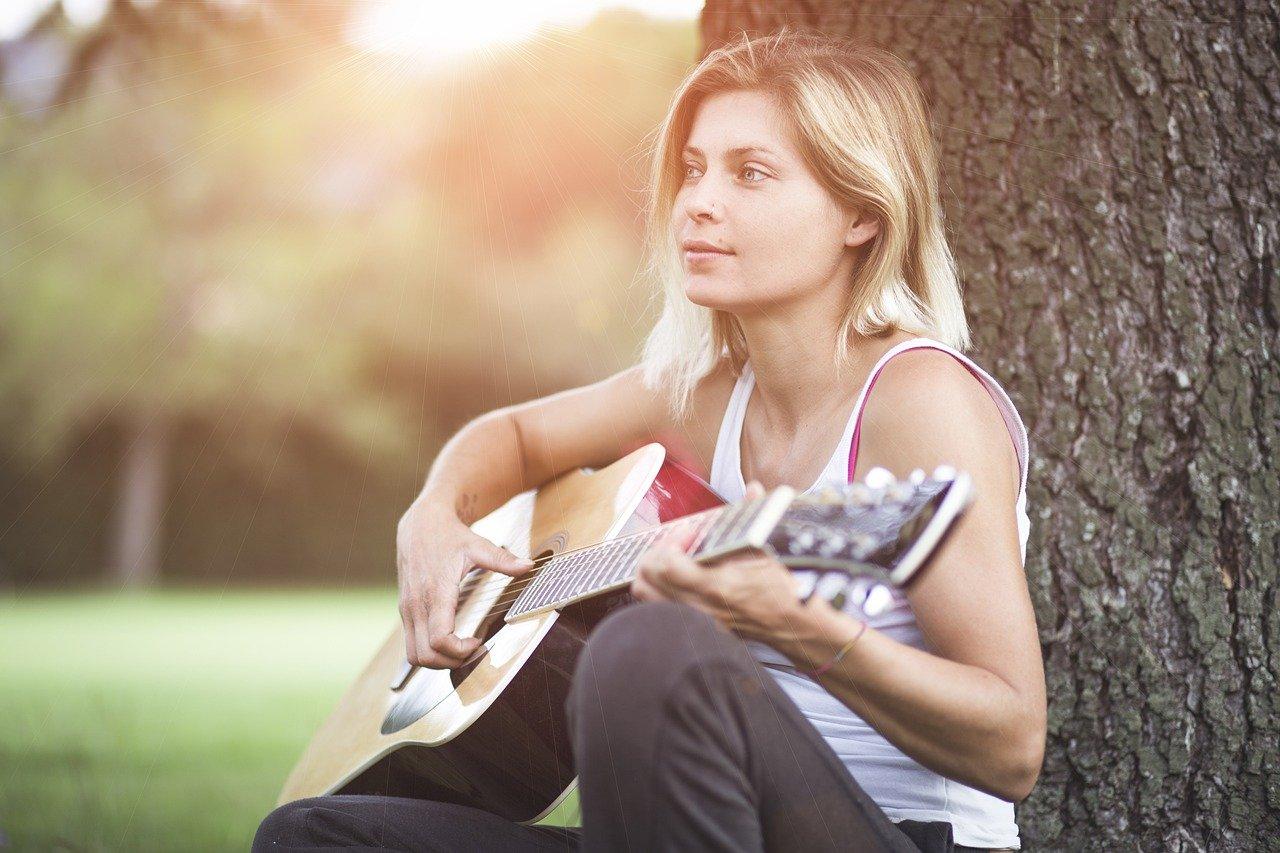 Dziewczyna gra na gitarze pod drzewem
